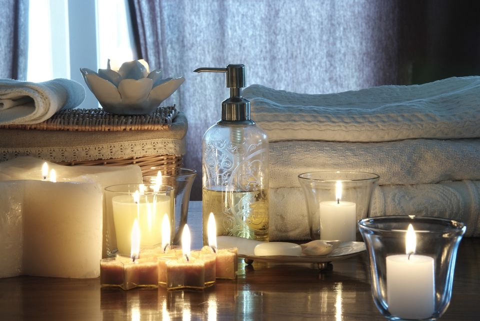 Candles, soaps, and bath towels adorn a cozy home spa bathroom