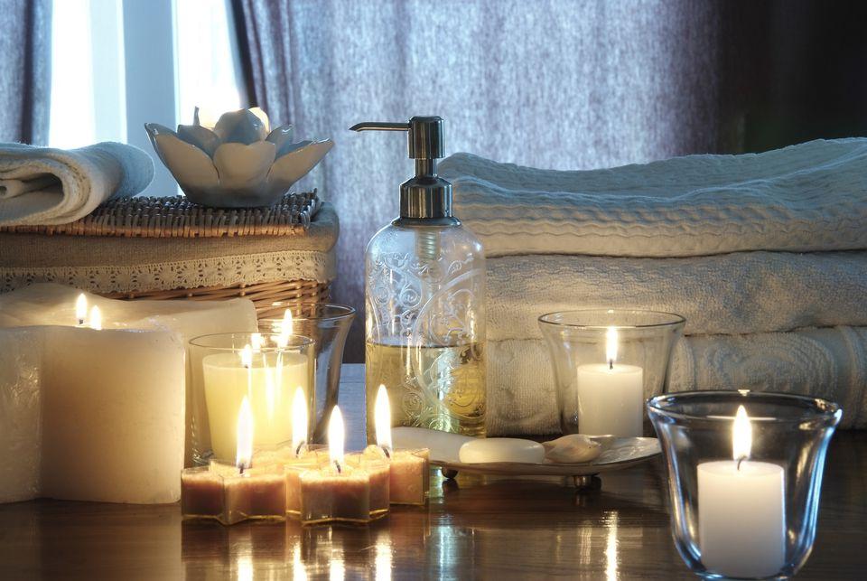 Candles, soaps, and bath towels adorn a cozy home spa bathroom