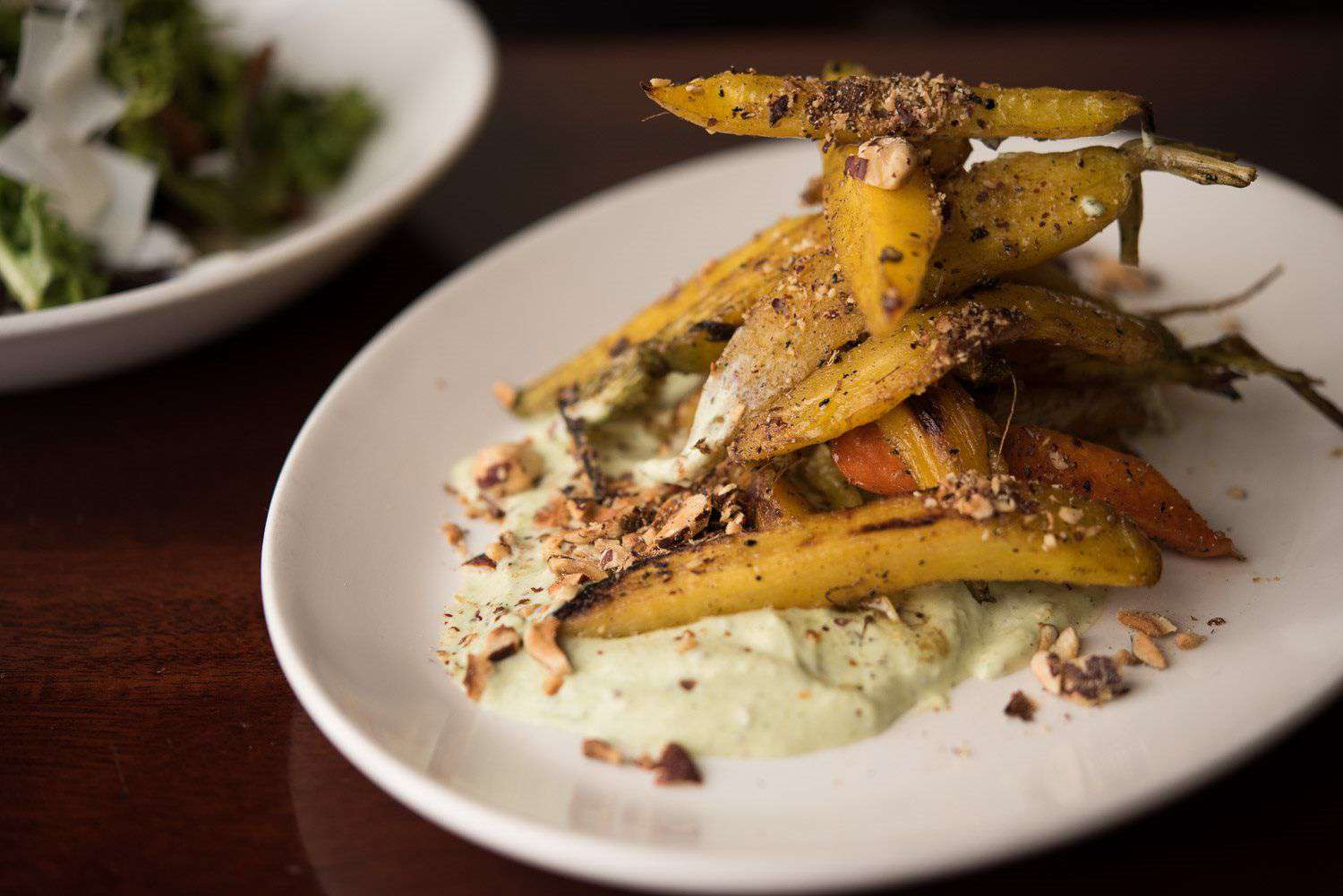 Roasted carrots onto of a pale green sauce, topped with crushed nuts