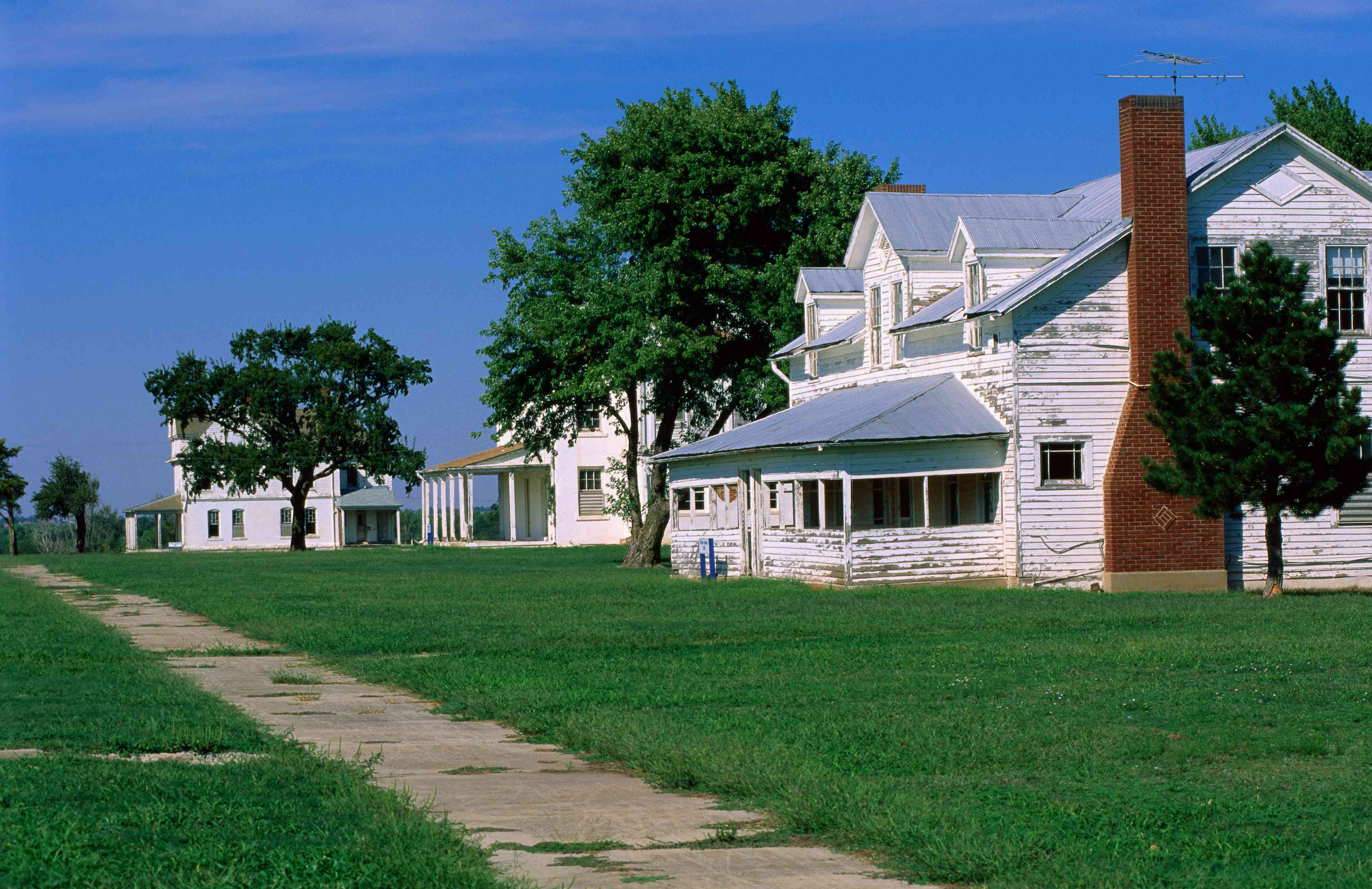 Historic white wooden buildings with green lawns and a small, cracked sidewalk