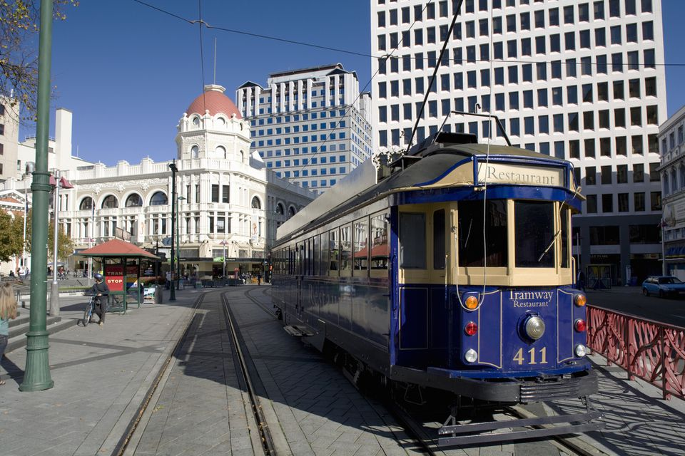 dark blue tram with white buildings in background