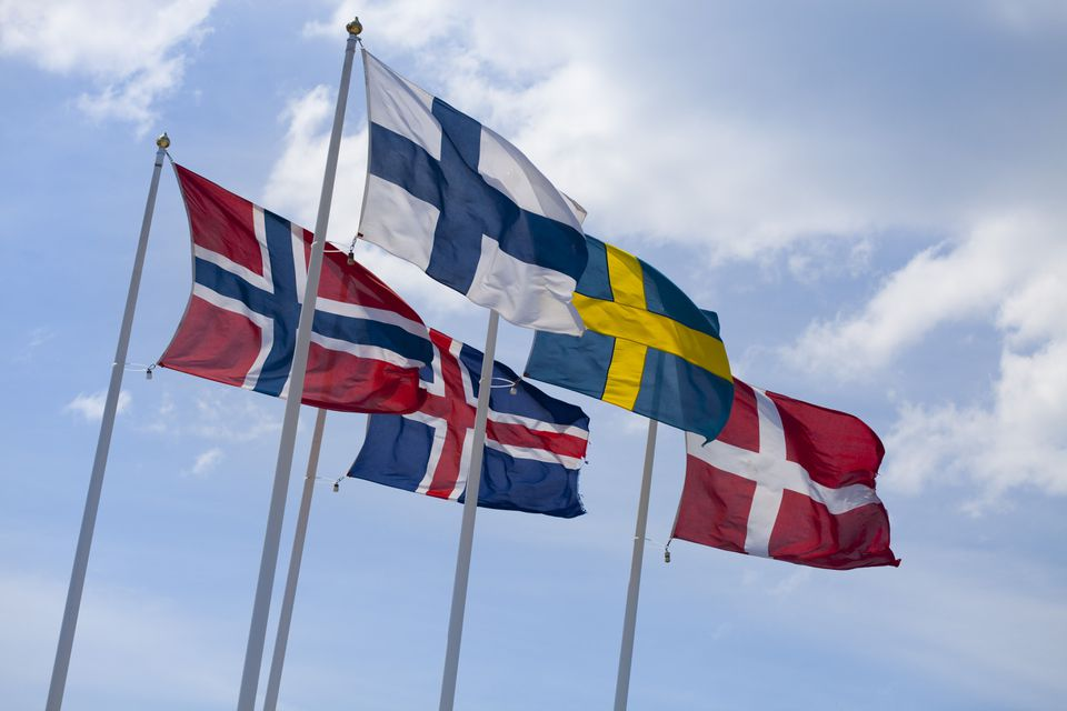 Flags of the Nordic countries on flag poles against blue sky