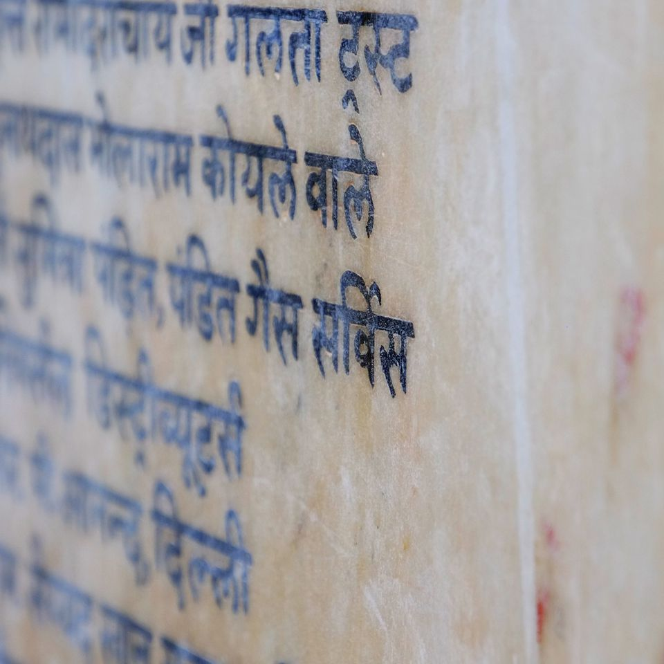 Close-Up Of Hindi Script On Marble