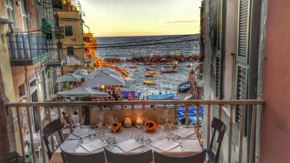 Table on a pation with views of busy harbor in riomaggiore, cinque terre