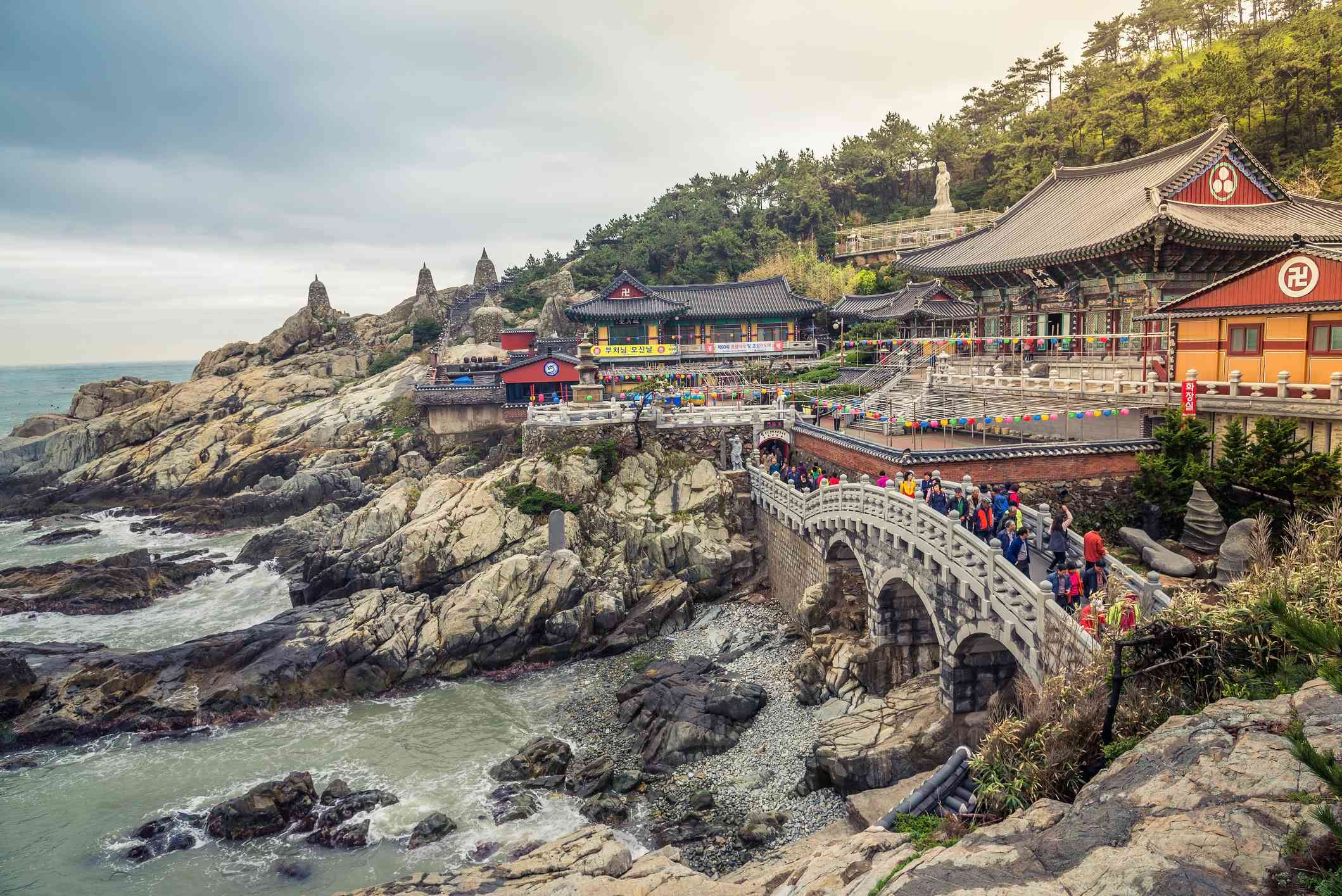 Haedong yonggungsa temple on the seaside in Busan , South Korea with colorful lanterns around the temple's paths