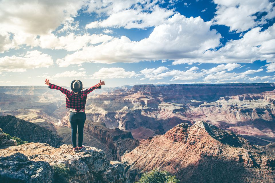 woman overlooking the grand canyon with arms raised