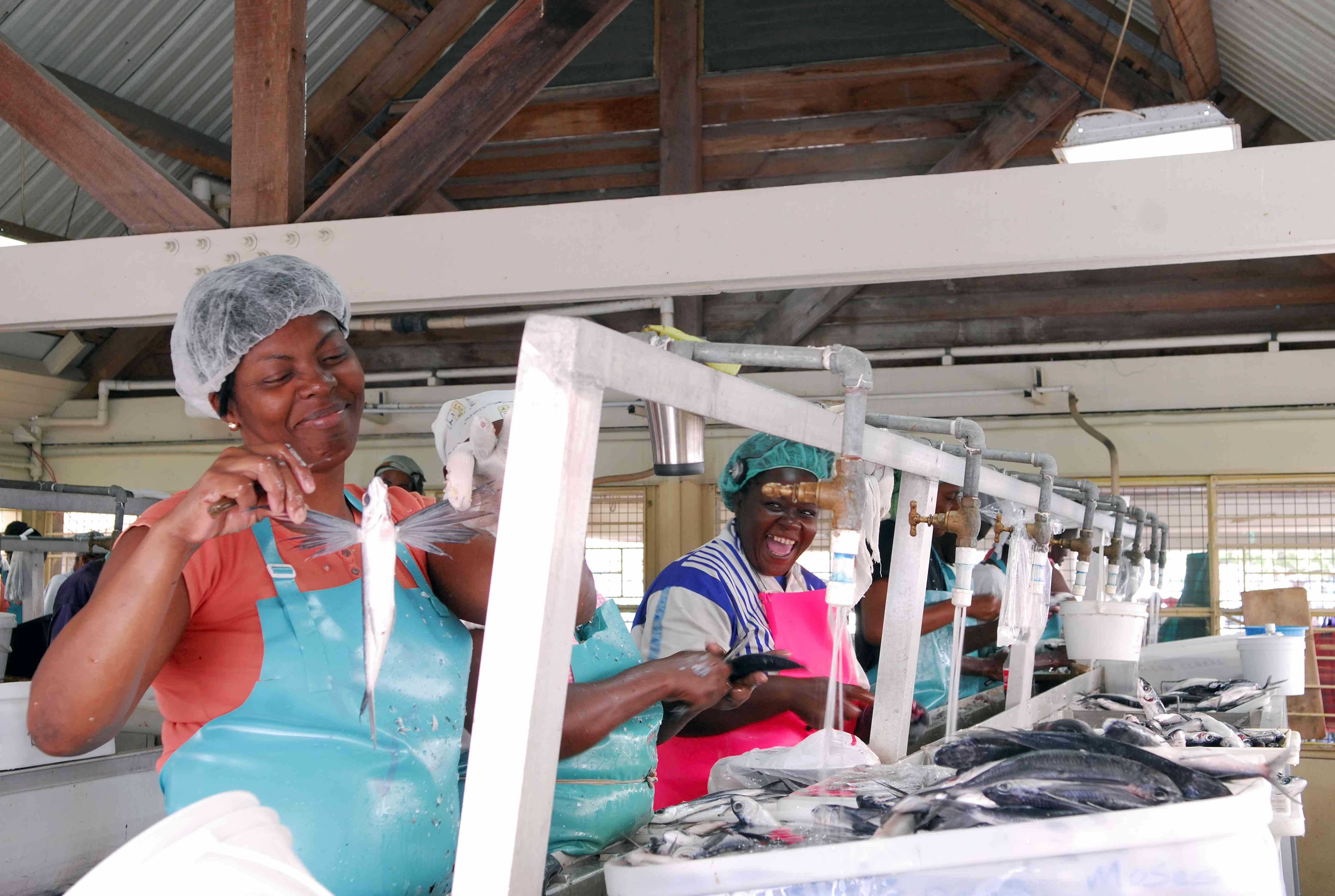 mujer trabajadora en el mercado de pescado de Barbados sosteniendo el pez volador
