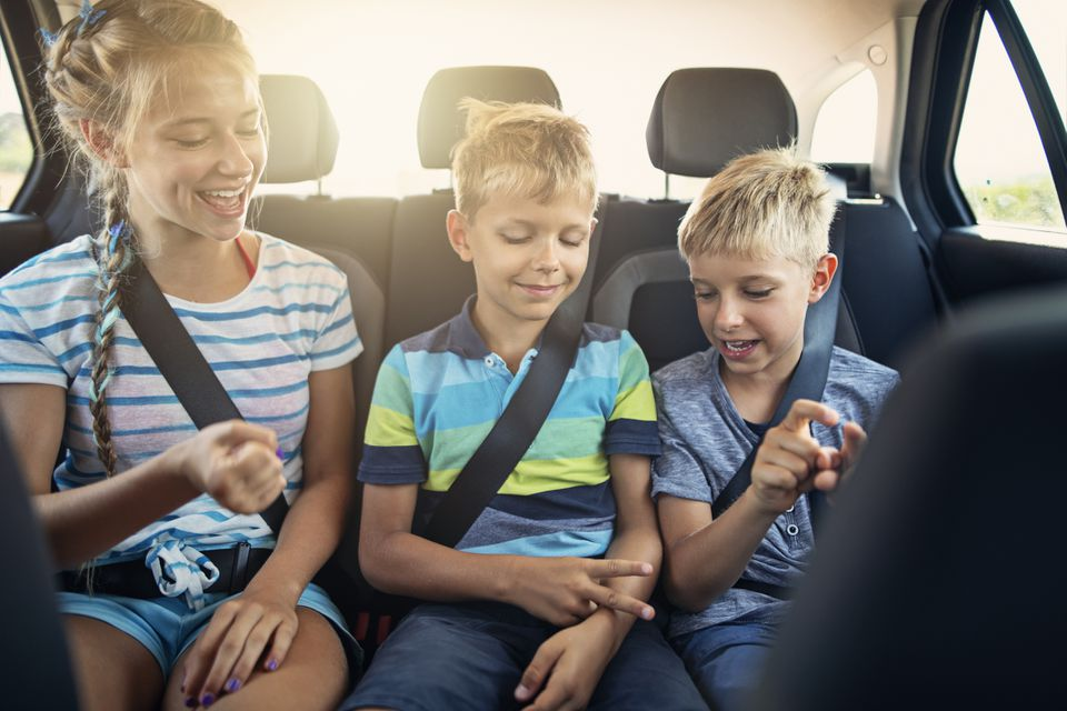 Kids playing rock, paper, scissors game in the car.