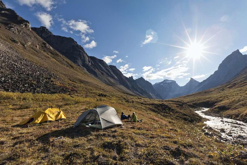 Los mochileros acampan junto a un pequeño arroyo en una montaña de vailley