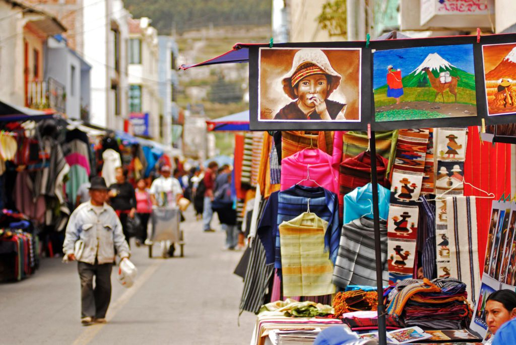 Ecuador, Otavalo, view of a series of realistic paintings exhibited at a stall on a street market with people walking in market and looking at variety of objects displayed for sale