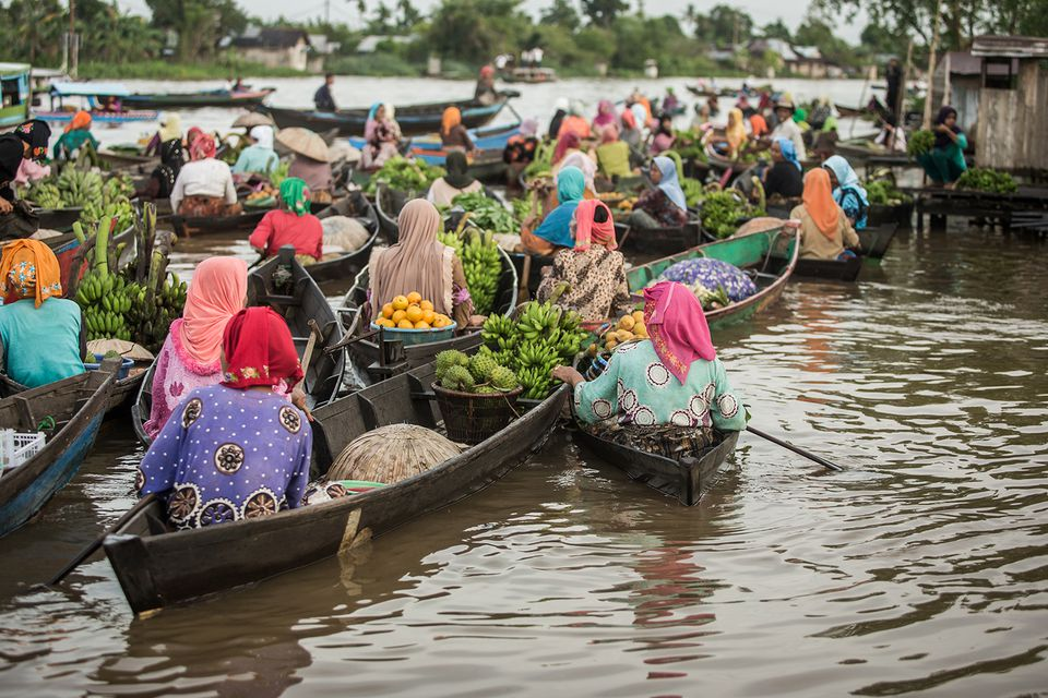 Market traders in traditional colourful clothing at a floating market