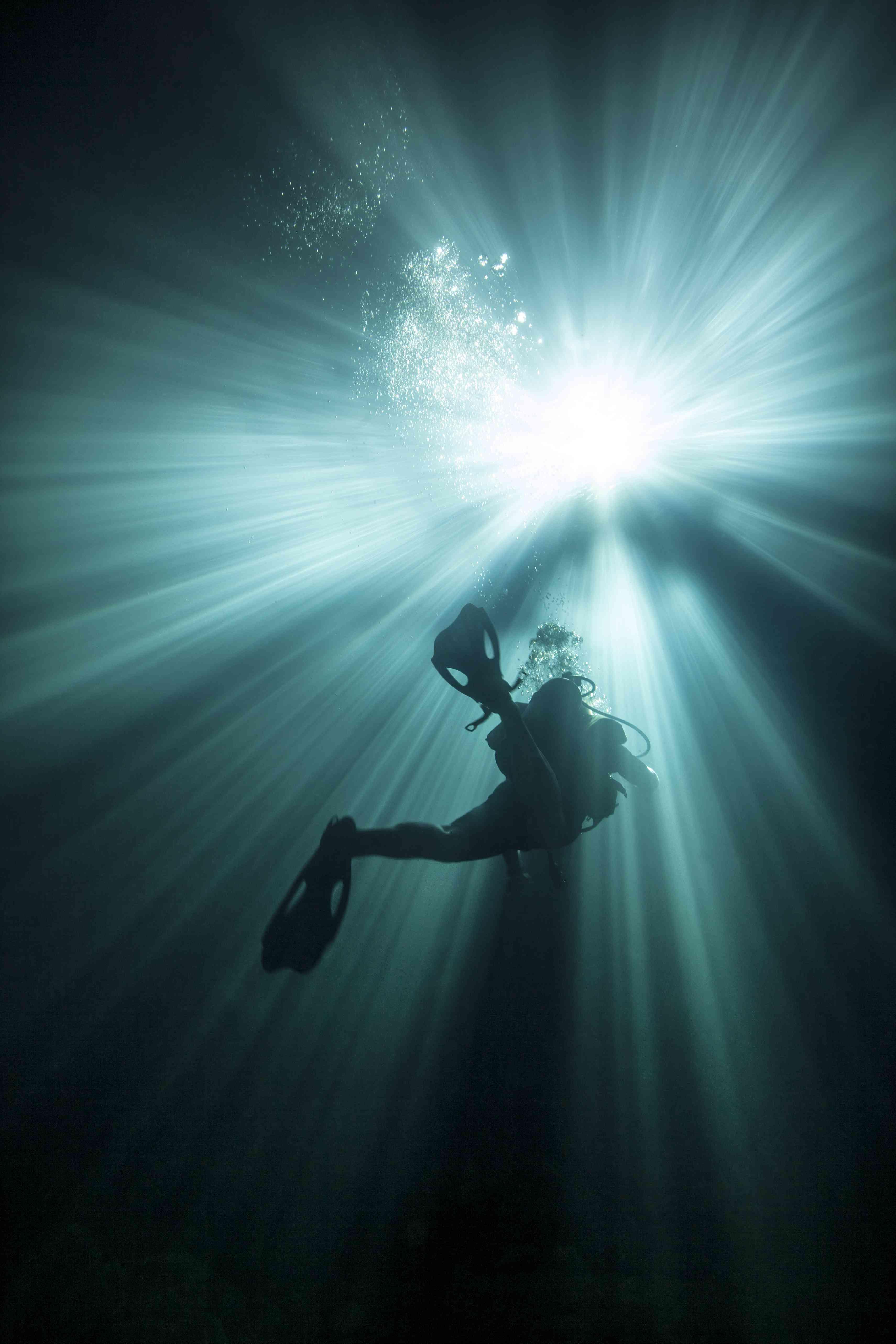 A scuba diver ascends into the light emanating above.