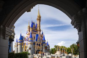 Pink and blue Cinderella's castle in Disney World framed by an arch