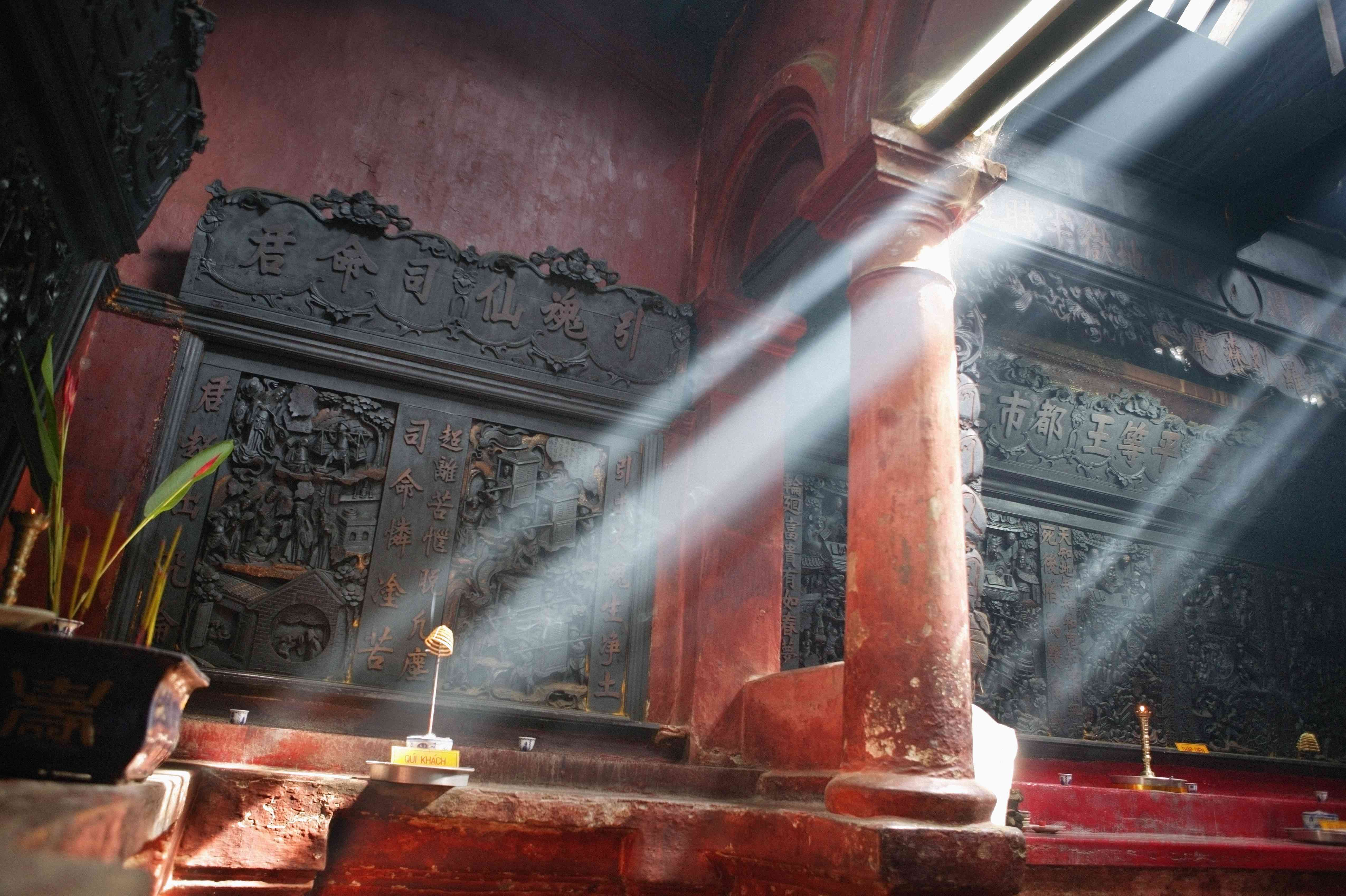 black carved wooden altar with shafts of light coming through