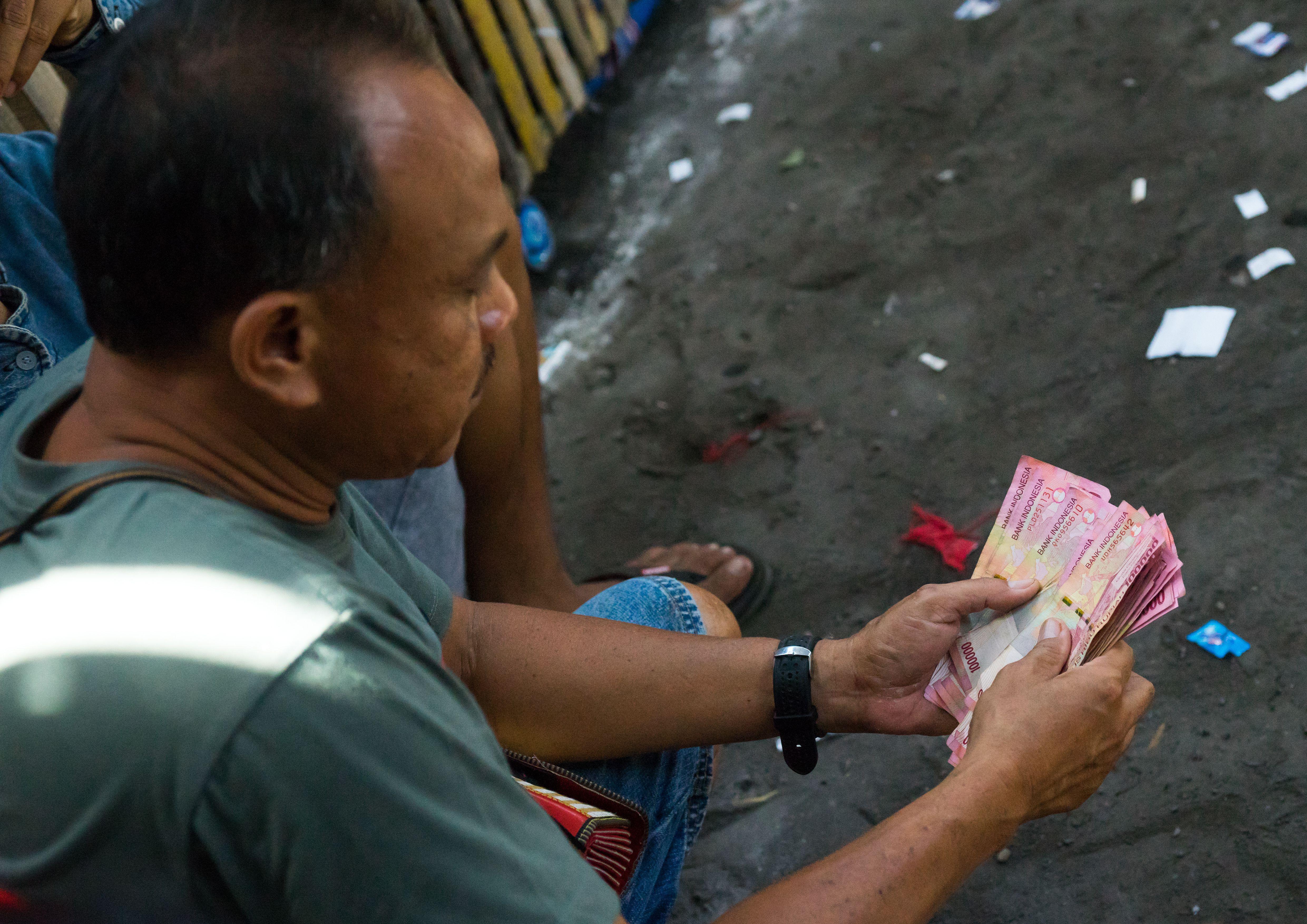 Hombre contando dinero en Bali