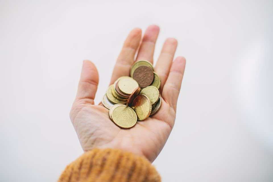 Woman's hand holding foreign coins