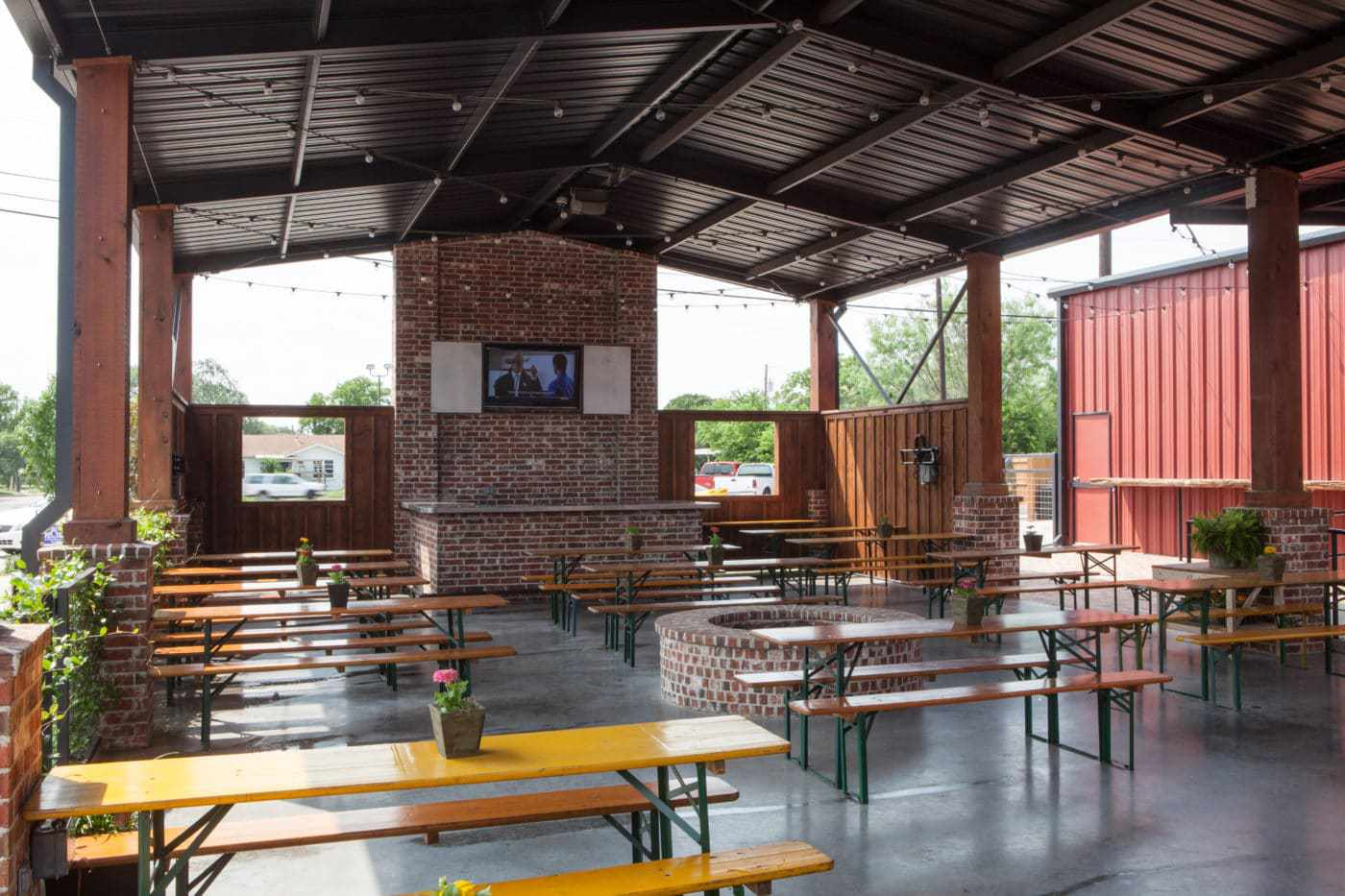 Opensided barn with orange picnic tables at Viteks BBQ