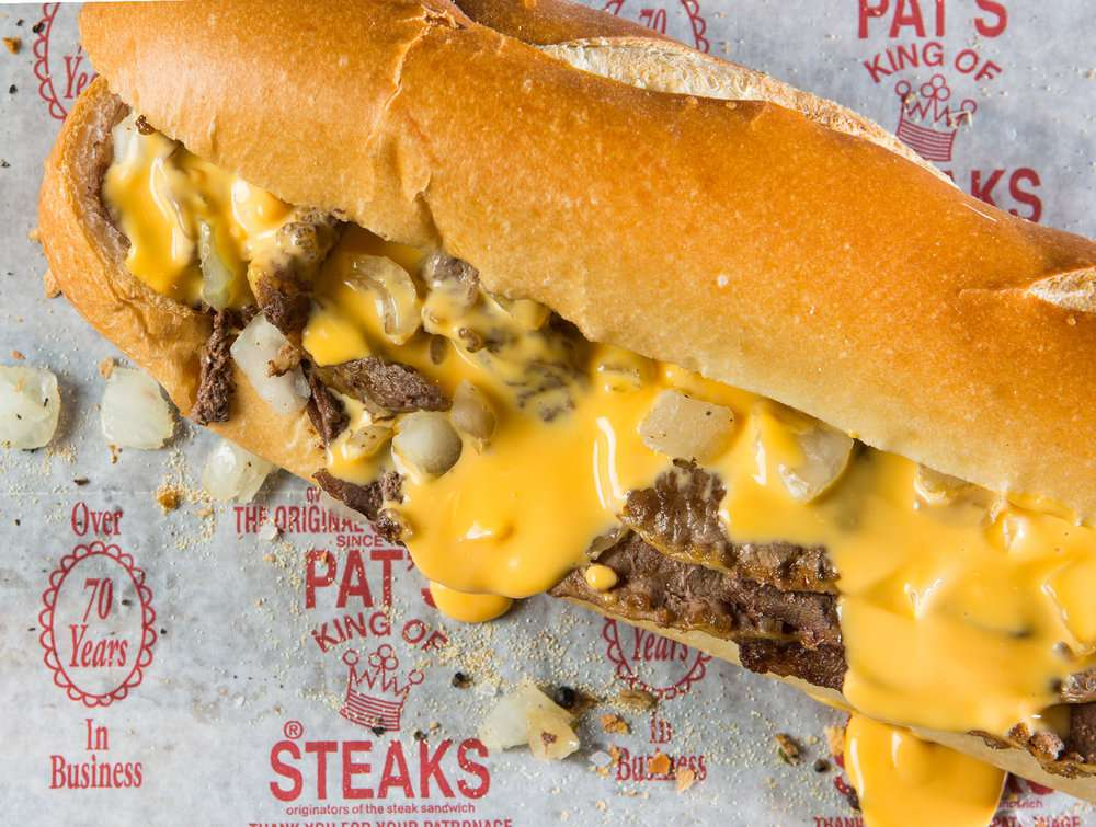 Philly cheesesteak con Cheese Whiz y cebolla en un papel que dice Over 70 Years in Business y Pat's King of Steaks