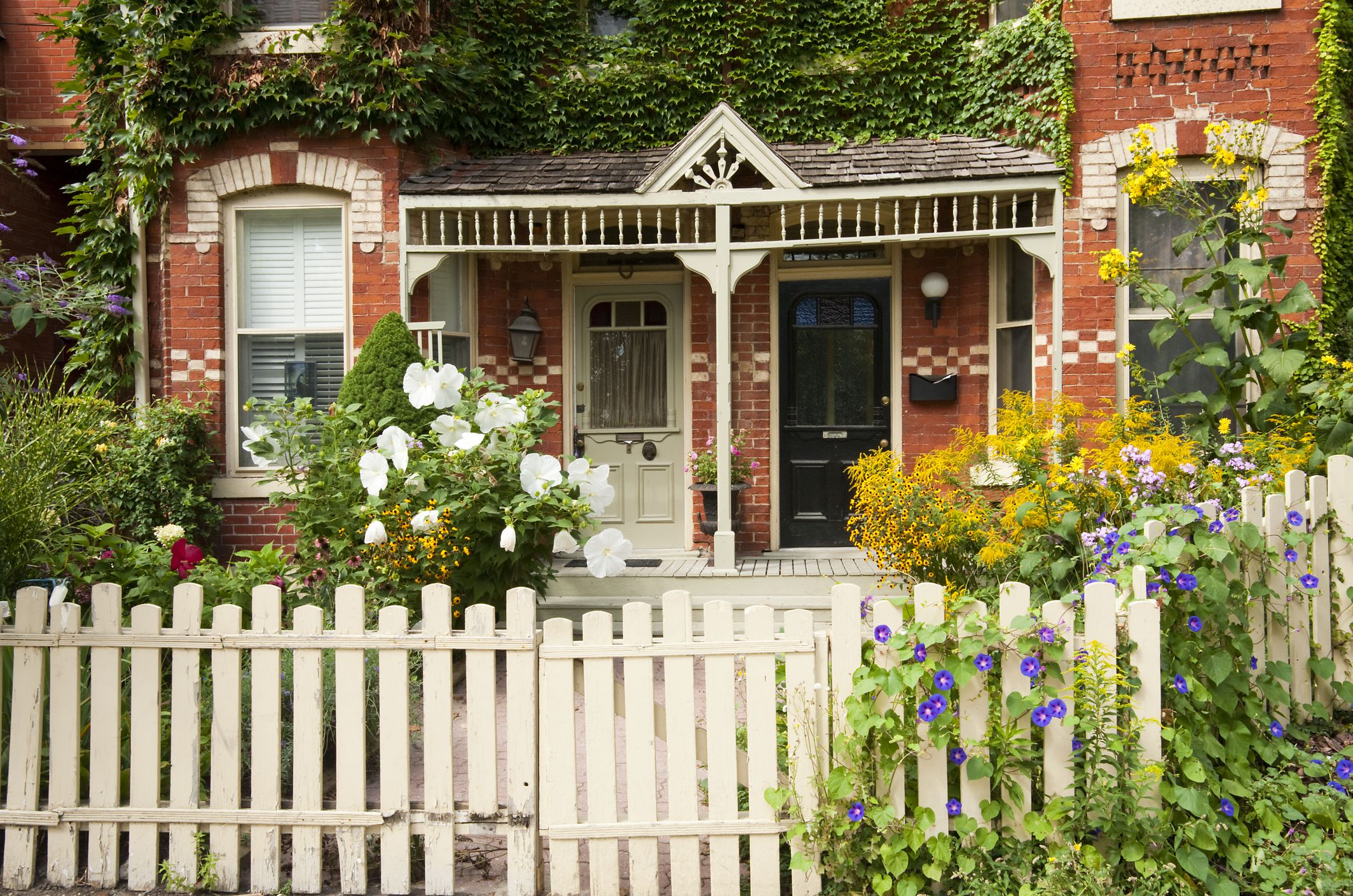 Old style red brick row houses with a white picket fences