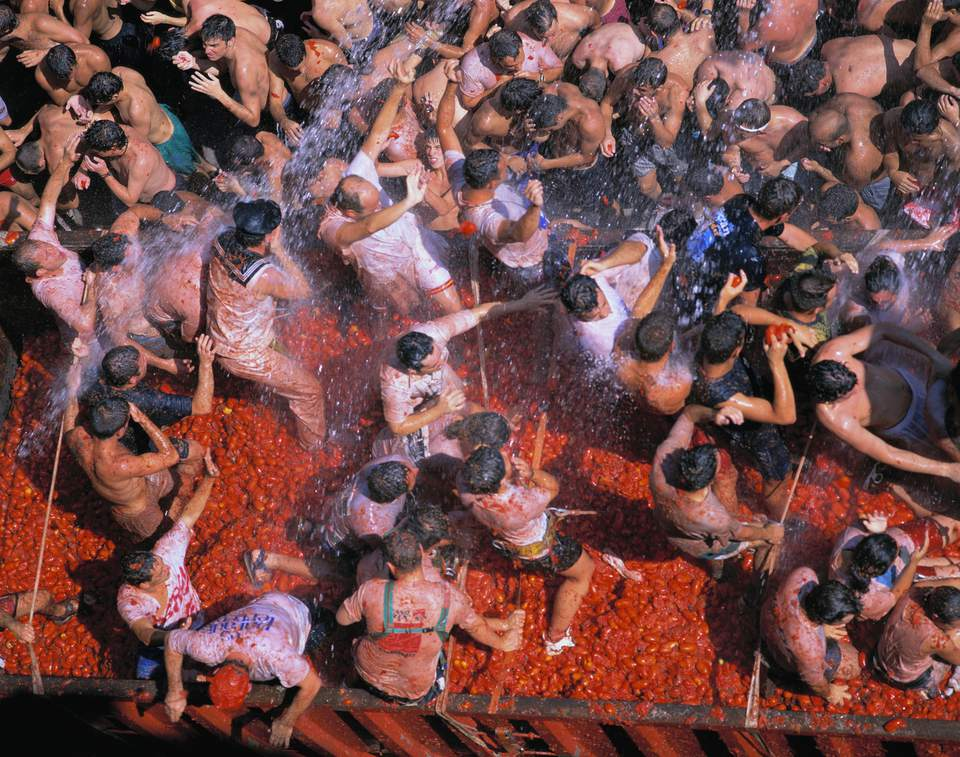 Combatants pelt each other with tomatoes as water sprays over head during the annual Tomatina Festival in Bunyol, Spain.