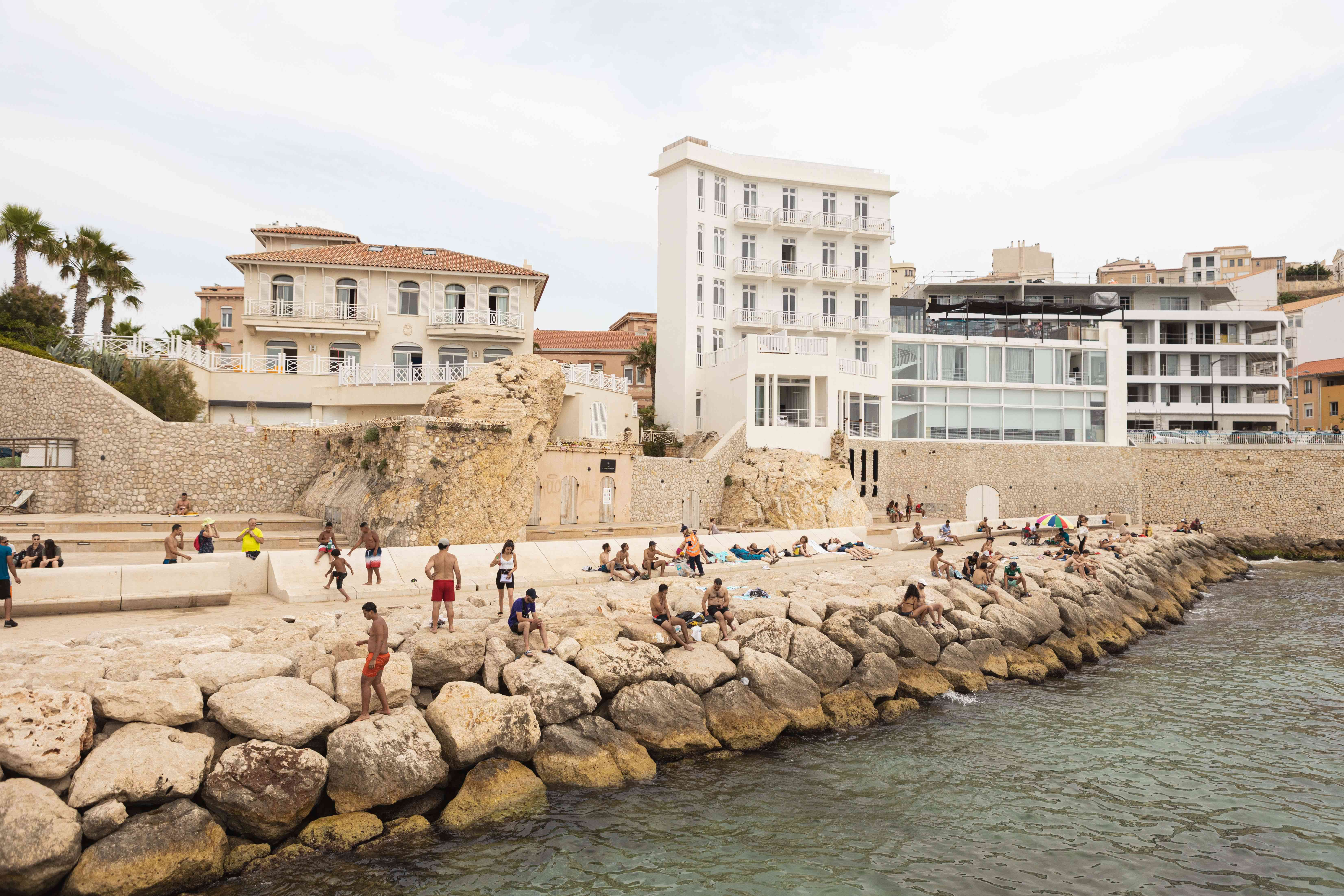 People on the rocky edge at Catalans Beach