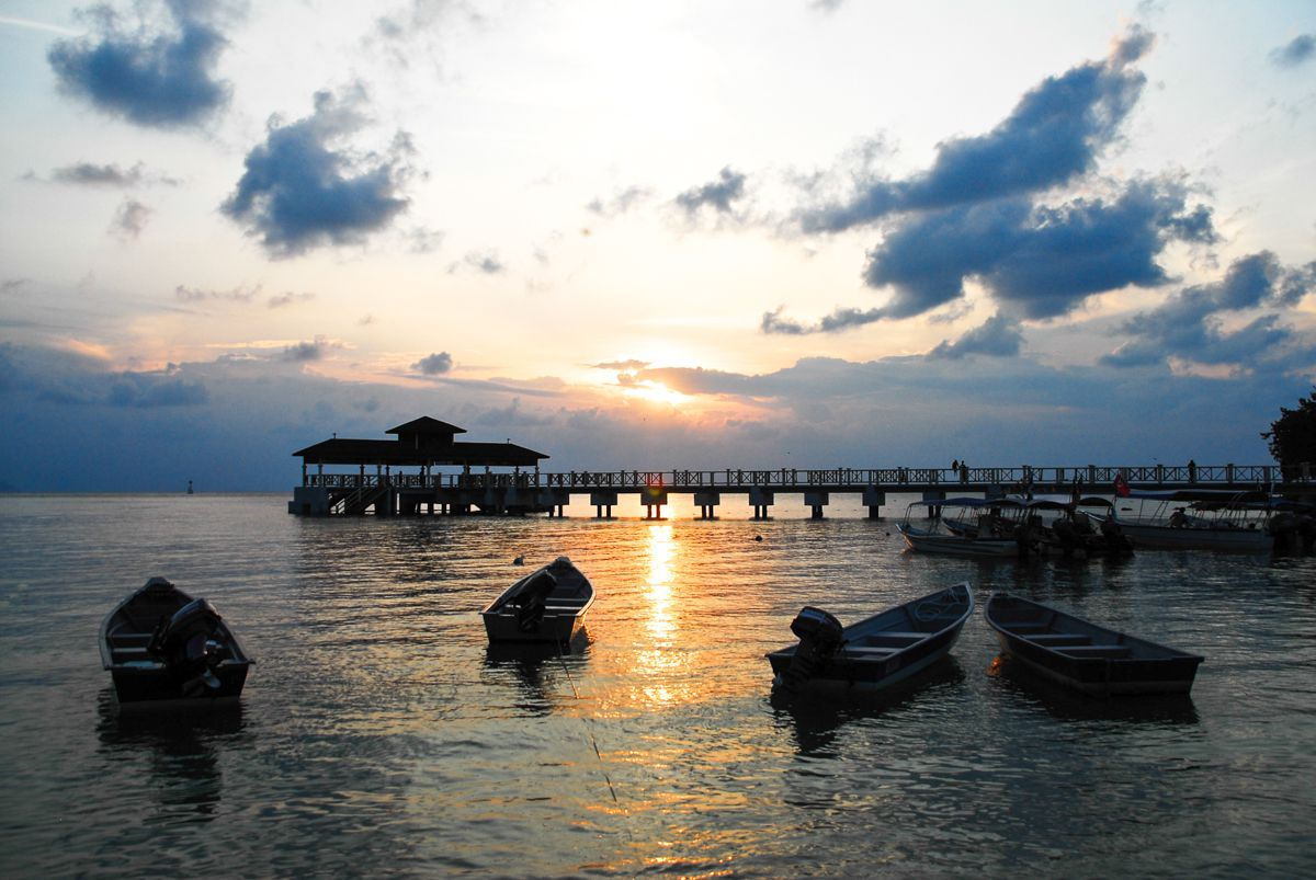 a dock on the Perhentian Islands during sunset with boats in the foreground
