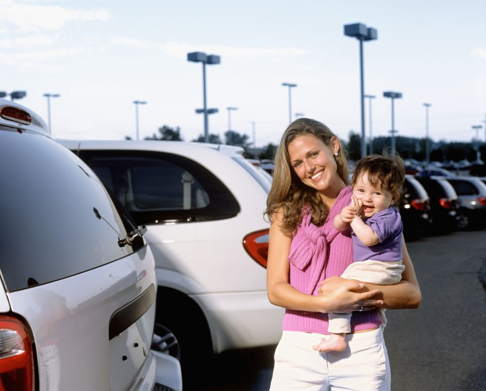 mom holding baby in parking lot