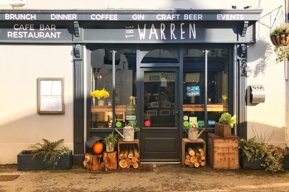 Black entryway to a restaurant (The Warren) with decorative wooden boxes and small logs on either side of the door