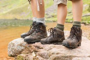 Low section of hikers in hiking boots atop rock.