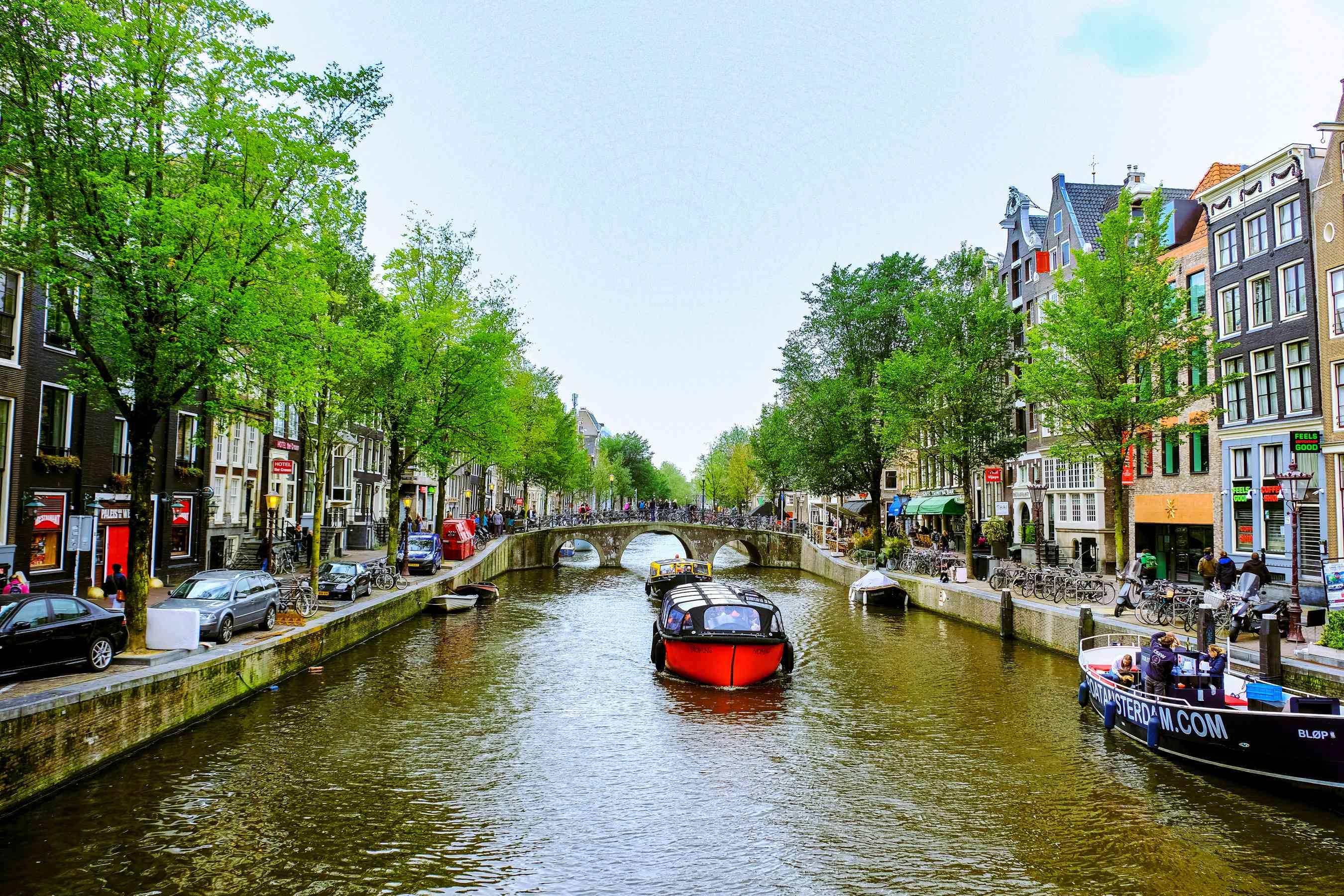 Un pequeño bote navegando por un canal en Amsterdam