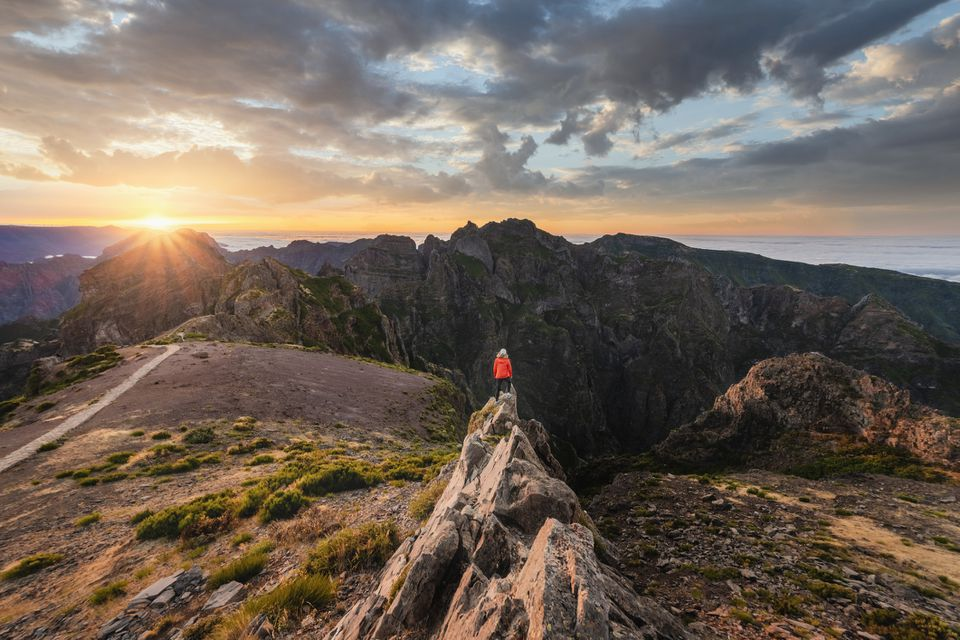 Woman standing on top of a rock admiring sunset at Pico do Arieiro, Madeira, Portugal