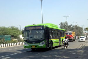 Large, green bus on crowded street