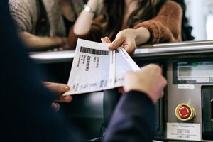 Passenger hands paper tickets to airport employee