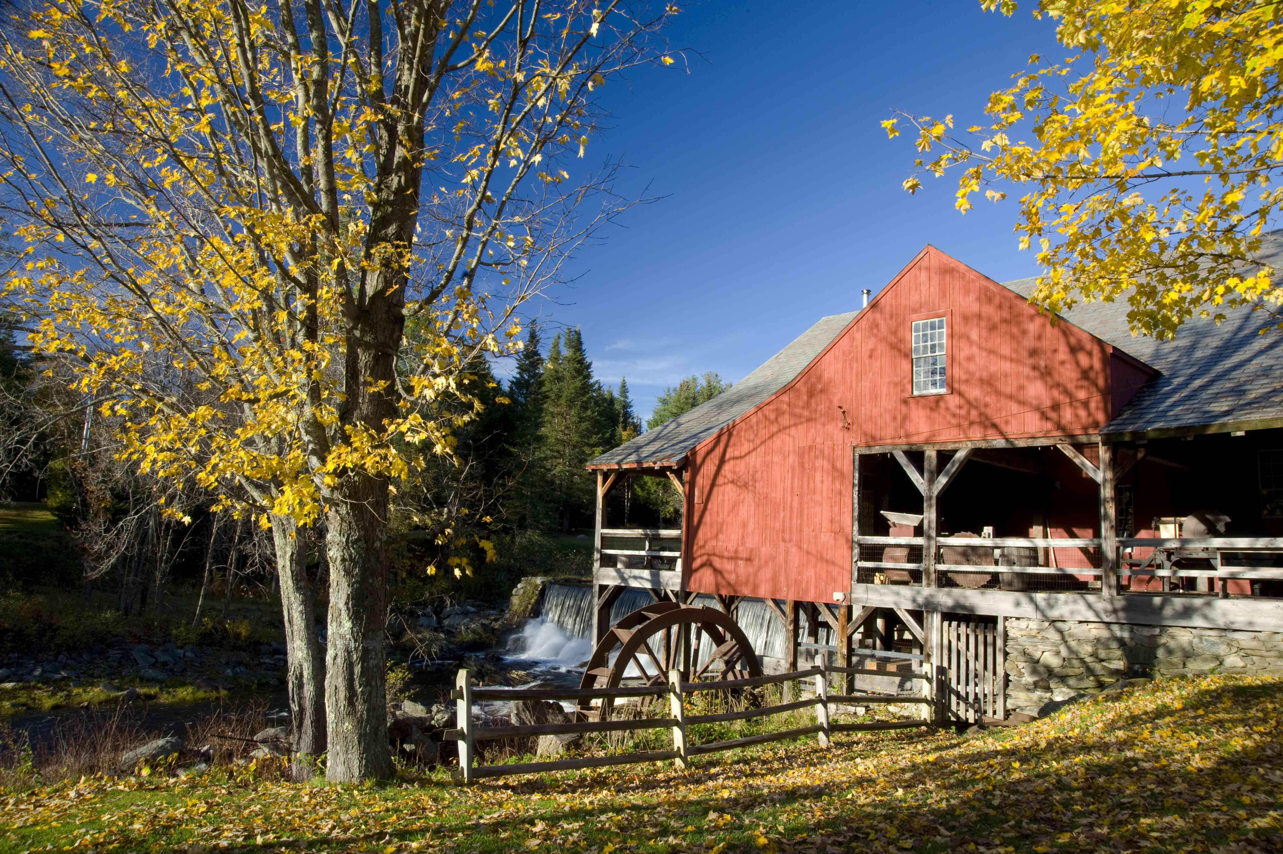 Old, red mill and waterfall surrounded by autumn leaves in Weston, Vermont