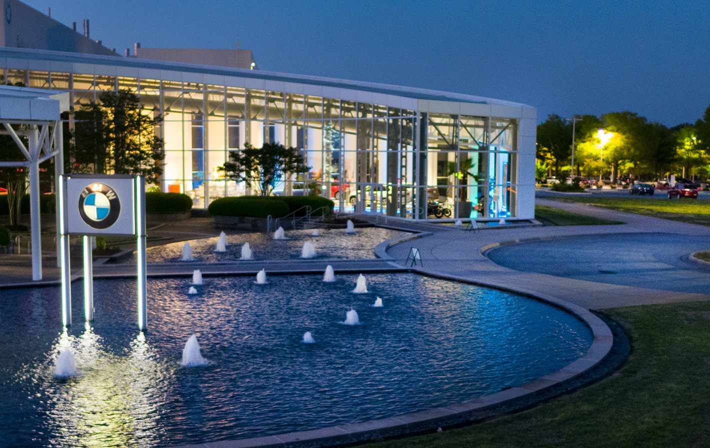 Fountain with a BMW sign in it in front of a low, modern glass and steel building