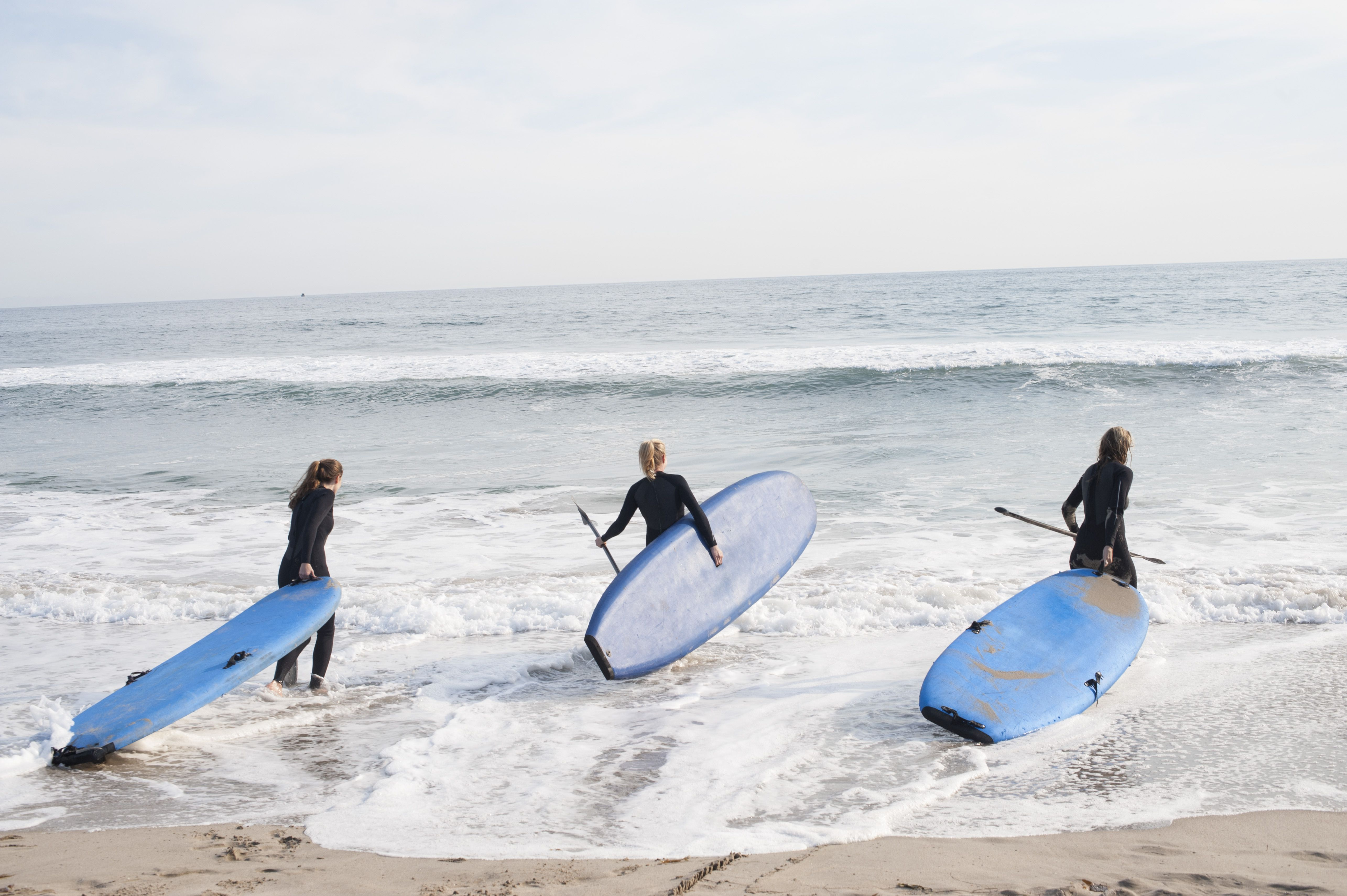 3 woman going surfing