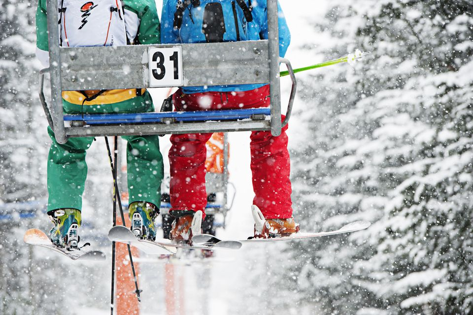 Skiers' legs hang from a chairlift in a snowy forest
