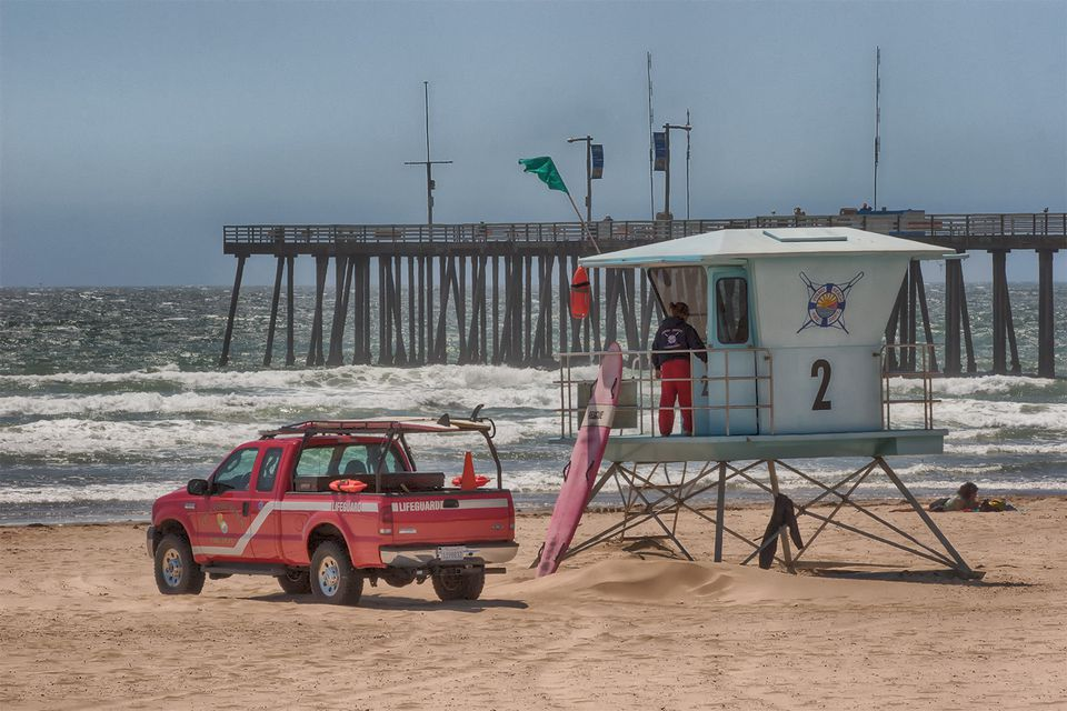 A lifeguard at the the lifeguard stand at Pismo Beach, with an emergency vehicle and longboard set against the pier and crashing waves