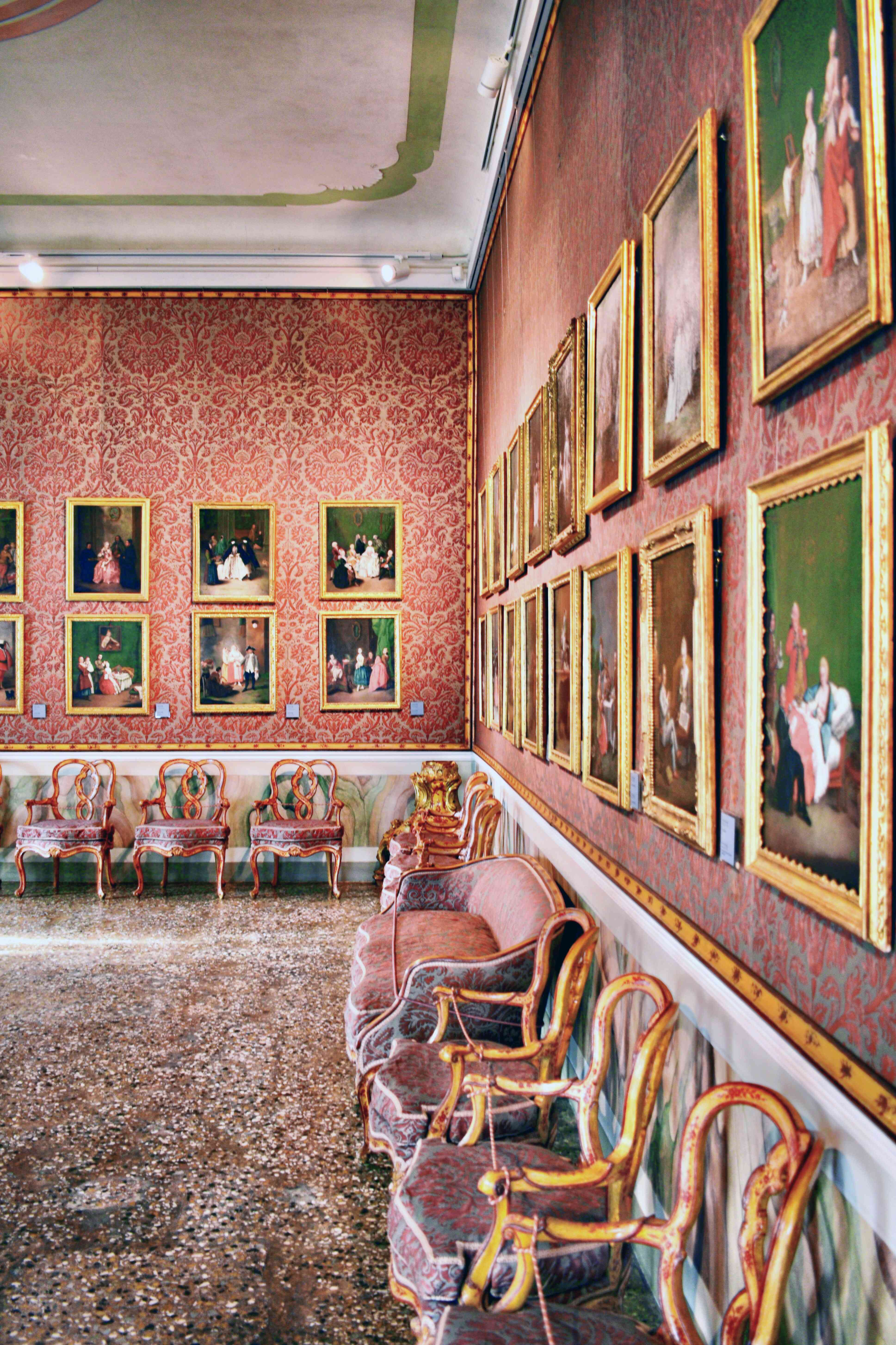 A bright pink room with green portraits and pink seats