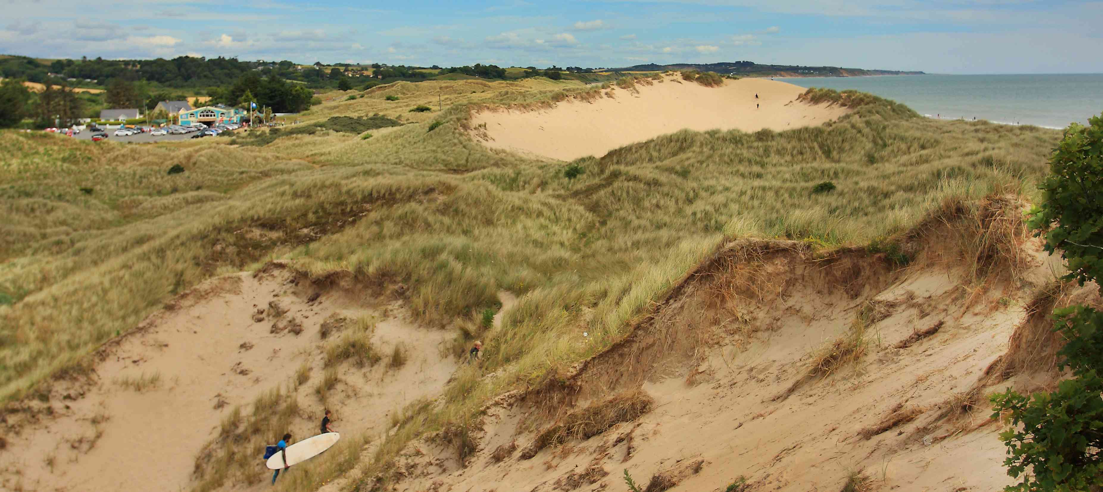 surfers walk up dunes in Ireland
