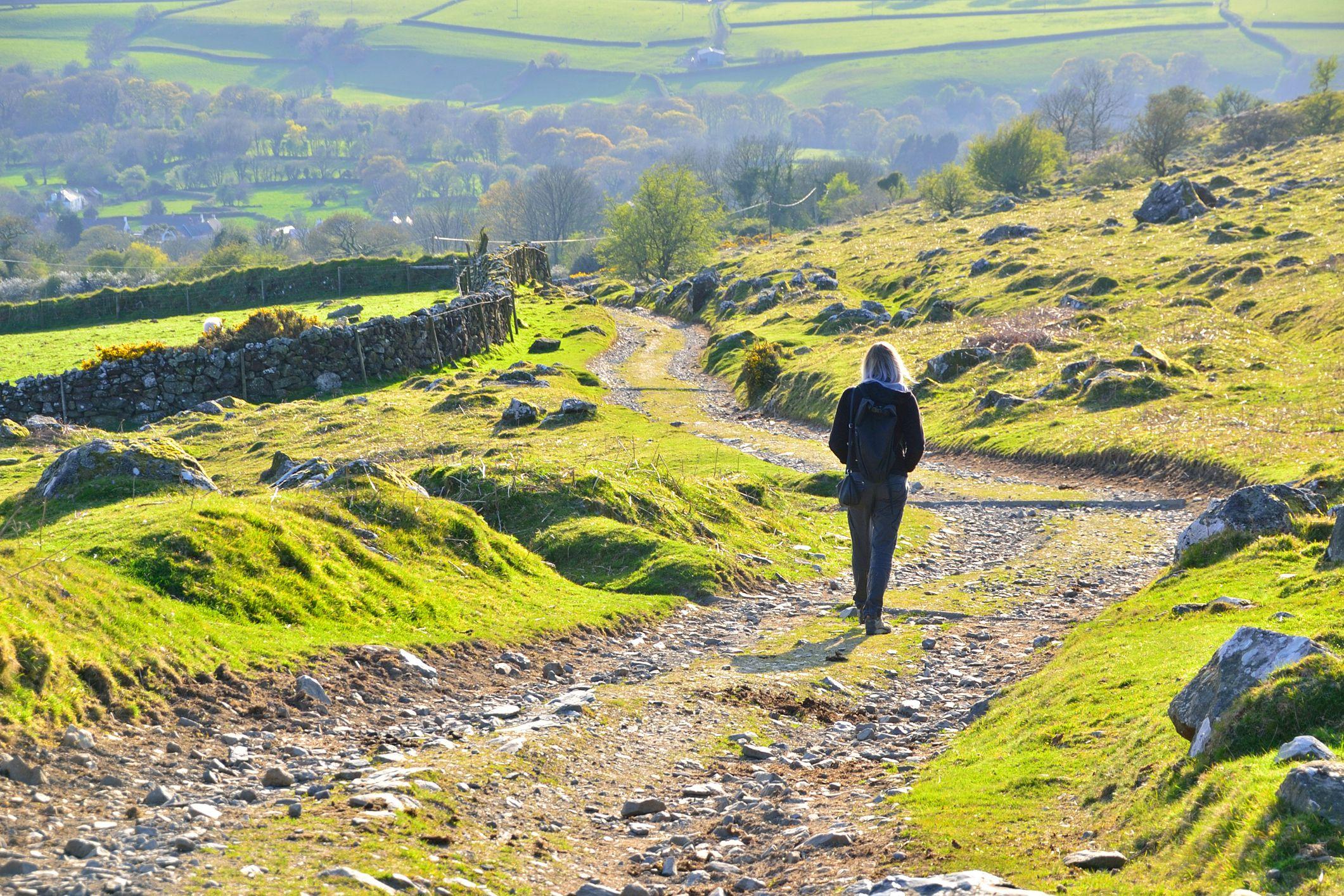 A woman walks around the barren moorland alone in Dartmoor National Park, Devon England UK