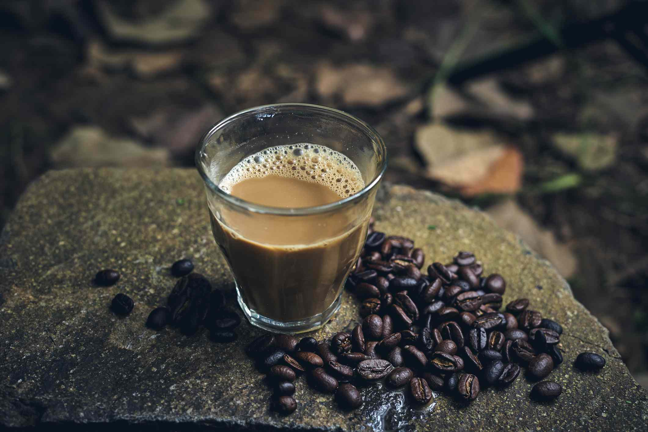 A glass of Traditional Indonesian Coffee with milk on a rock in a forest with roasted coffee beans