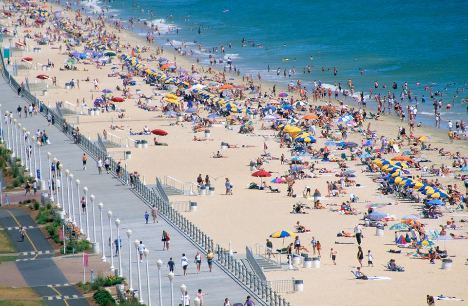 People relaxing and swimming along Virginia Beach and walking on the boardwalk.