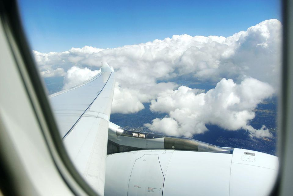 view of the sky out of the window of an airplane with partial view of the wing