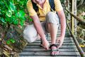 A tourist crouching down to fix his hiking sandals