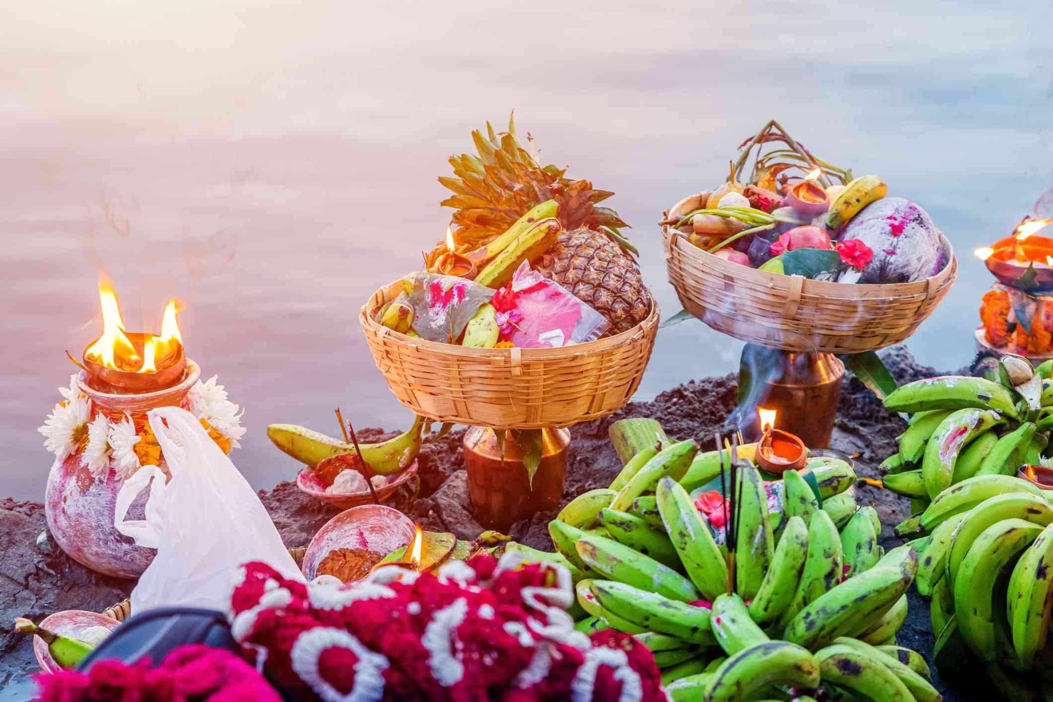 bunches of green bananas, baskets of fruit and candles sitting on rocks beside a river