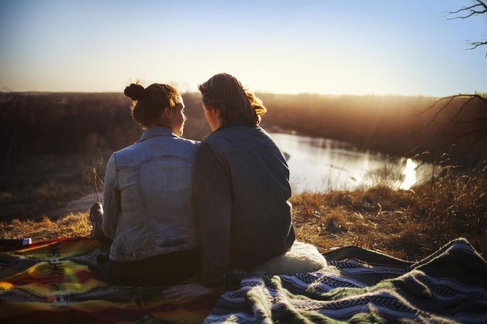 Couple on blanket by lake.