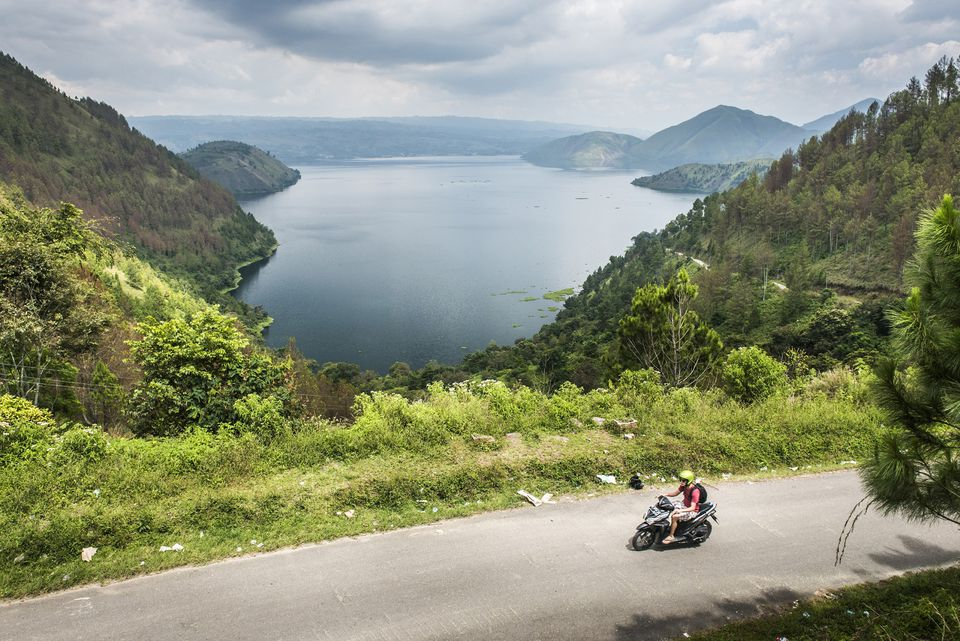 Tourist motorbiking along Samosir Island road, with Lake Toba view