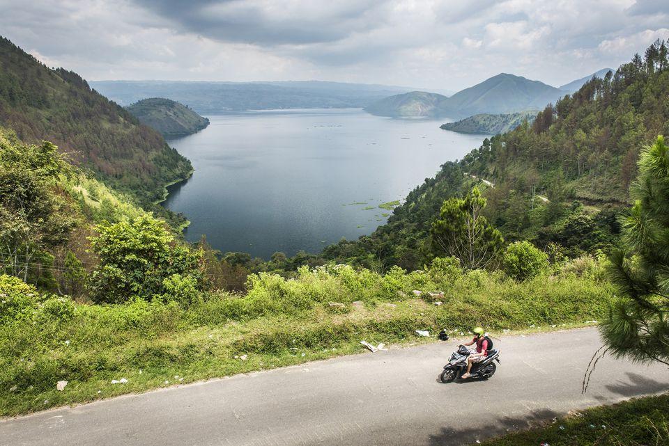Motociclismo turístico a lo largo de la carretera de la isla Samosir, con vistas al lago Toba