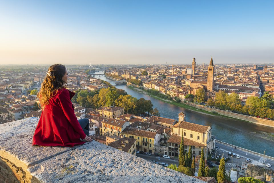 A young woman admires the view of Verona old town from Castel San Pietro